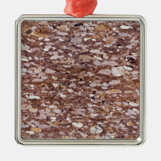 Surface of a red sandstone with siliceous geods metal ornament