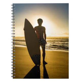Surfer silhouette during sunrise note books