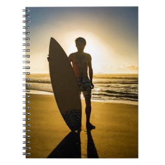 Surfer silhouette during sunrise notebooks