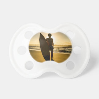 Surfer silhouette during sunrise pacifier