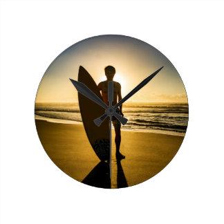 Surfer silhouette during sunrise round clock