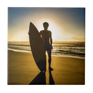 Surfer silhouette during sunrise tile