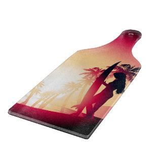 Surfing girl at sunrise cutting board