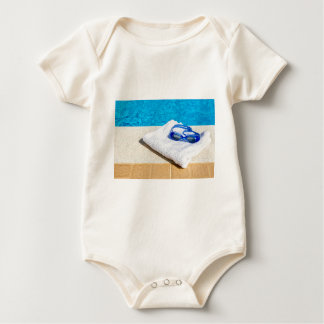 Swimming goggles and towel near swimming pool baby bodysuit