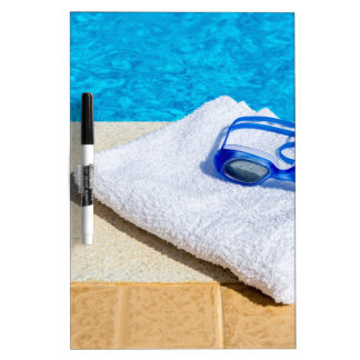 Swimming goggles and towel near swimming pool dry erase board