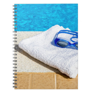 Swimming goggles and towel near swimming pool notebooks