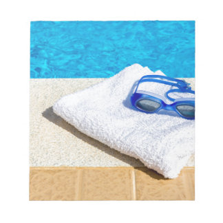 Swimming goggles and towel near swimming pool notepad