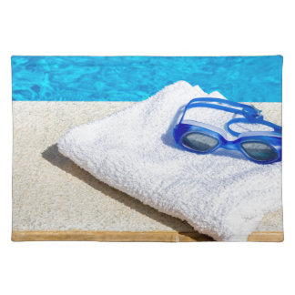 Swimming goggles and towel near swimming pool placemat