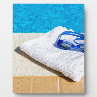 Swimming goggles and towel near swimming pool plaque