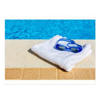 Swimming goggles and towel near swimming pool postcard