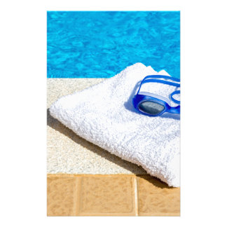 Swimming goggles and towel near swimming pool stationery
