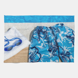 Swimming trunks goggles and towel at pool