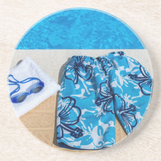 Swimming trunks goggles and towel at pool beverage coasters