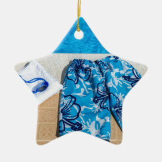 Swimming trunks goggles and towel at pool ceramic star ornament