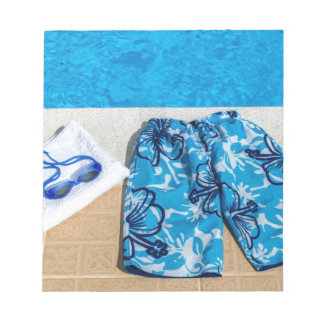 Swimming trunks goggles and towel at pool notepads
