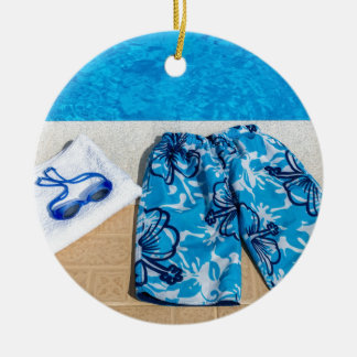 Swimming trunks goggles and towel at pool round ceramic ornament