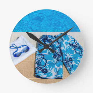 Swimming trunks goggles and towel at pool round clock