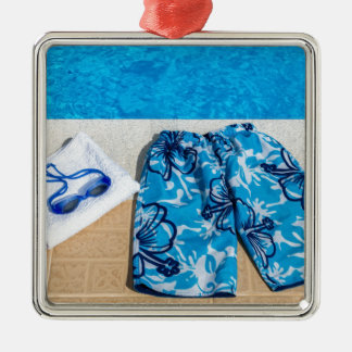 Swimming trunks goggles and towel at pool Silver-Colored square ornament