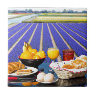 Table with food and drink near flowers field ceramic tiles
