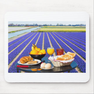 Table with food and drink near flowers field mouse pad