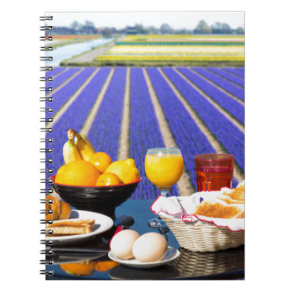 Table with food and drink near flowers field notebooks