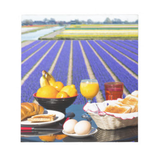 Table with food and drink near flowers field notepads