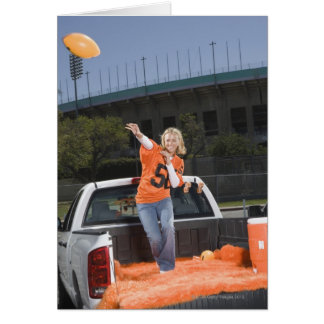 Tailgating woman throwing football greeting card