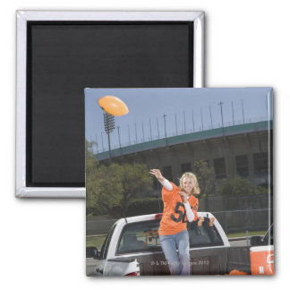 Tailgating woman throwing football square magnet