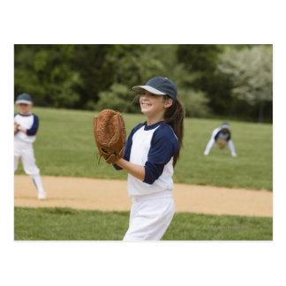 Tangage de fille dans le jeu de base-ball d'équipe carte postale