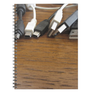 Tangle of dusty computer cables with sockets spiral notebook