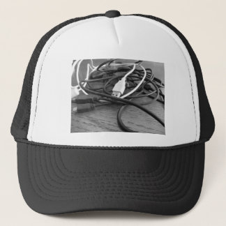 Tangle of dusty computer cables with sockets trucker hat