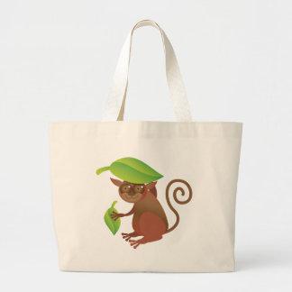 Tarsier hiding under a green leaf large tote bag