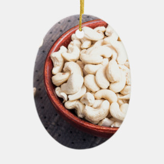 Tasty and healthy raw cashew nuts in a brown bowl ceramic oval ornament