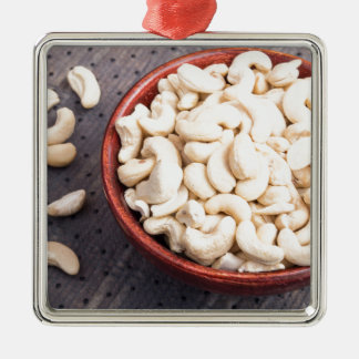 Tasty and healthy raw cashew nuts in a brown bowl Silver-Colored square ornament