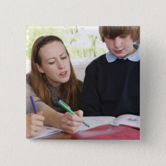 teacher assisting child with work in classroom 2 inch square button