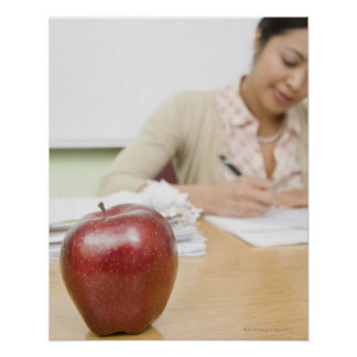 Teacher grading papers with apple in foreground posters