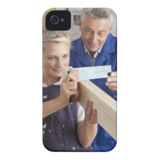 Teacher helping student measuring planed wood in Case-Mate iPhone 4 cases