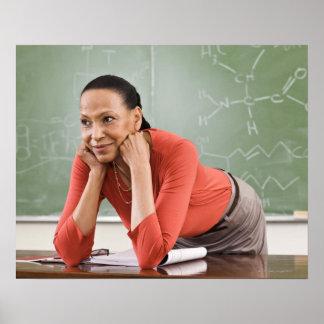 Teacher leaning on desk by chalkboard poster