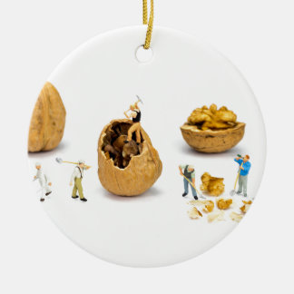 Team of miniature figurines transporting walnut ceramic ornament