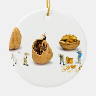 Team of miniature figurines transporting walnut round ceramic ornament