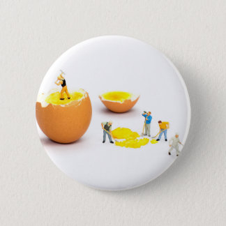 Team of miniature human figurines transporting egg 2 inch round button