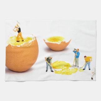 Team of miniature human figurines transporting egg hand towel