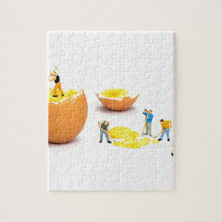 Team of miniature human figurines transporting egg jigsaw puzzle