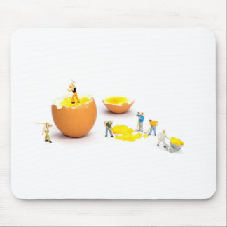Team of miniature human figurines transporting egg mouse pad
