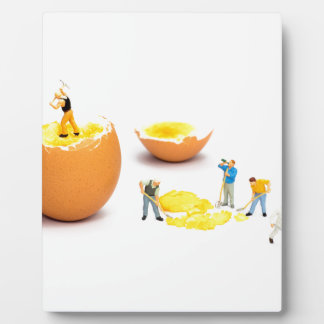 Team of miniature human figurines transporting egg plaque