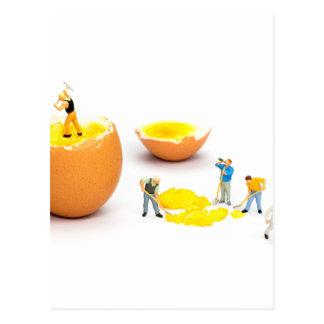 Team of miniature human figurines transporting egg postcard