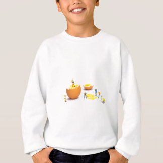 Team of miniature human figurines transporting egg sweatshirt