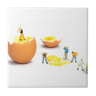 Team of miniature human figurines transporting egg tile