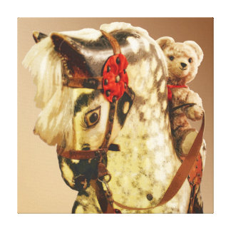 Teddy bear riding a rocking horse stretched canvas print