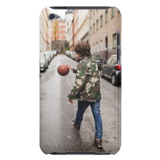 Teenage boy dribbling basketball iPod touch cases